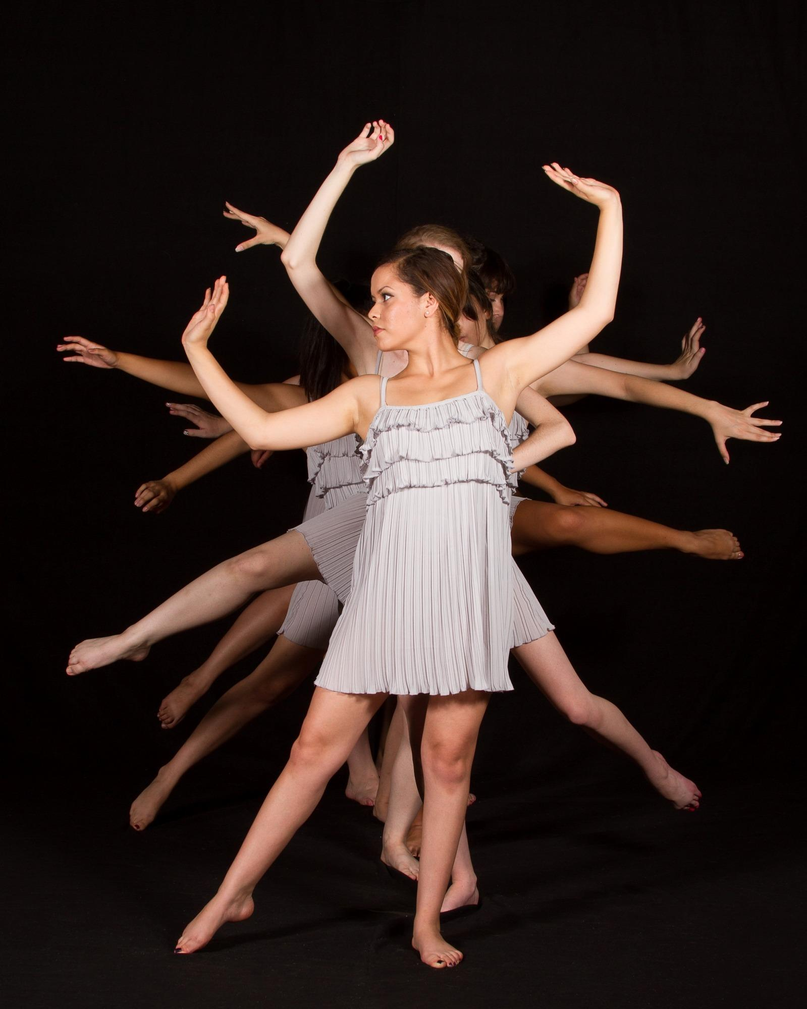 Group of dancers in a line reaching out with arms and legs.